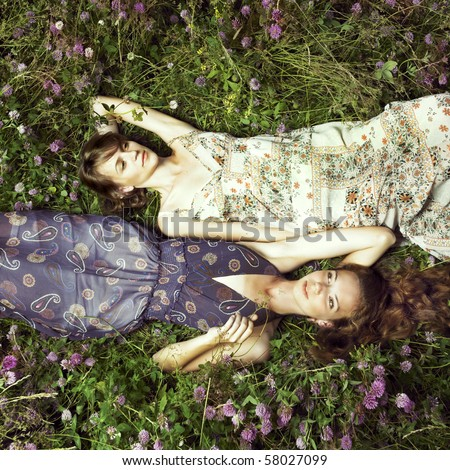 Two romantic girl lying on flower meadow