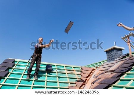 Two roofers transfer tiles across the roof by tossing them through the air - stock photo
