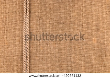 Two ropes lie on sackcloth, with space for your text - stock photo