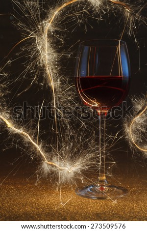 Two rose wine glasses on gold glitter surface lit by sparkling sticks - stock photo