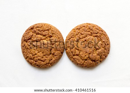 two round oatmeal cookies on a white background - stock photo