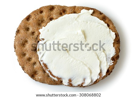 Two round rye crispbread isolated on white from above. Spread with cream cheese.