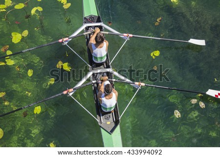 Two rowers in a boat, rowing on the tranquil lake  - stock photo