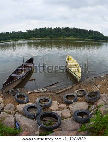 Two rowing boats moored on a river bank with old tires - stock photo