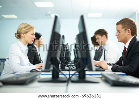 Two rows of businesspeople working on computers