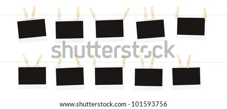 Two rows of five blank pieces of instant film hanging from clothespins on strings isolated on white.