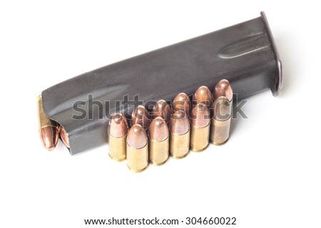Two rows of 9mm brass bullets and gun holder isolated on white background - stock photo