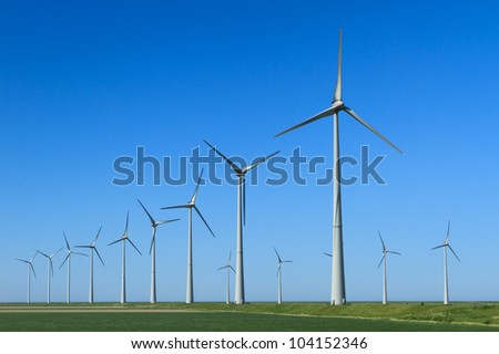 Two rows of modern wind turbines generating clean, renewable energy in the green countryside.