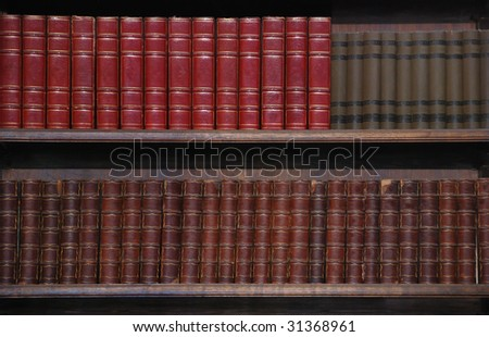 Two rows of old books on bookshelves. - stock photo