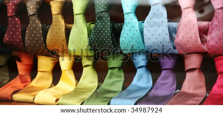 Two rows of varicolored silk neckties in a shop window - stock photo