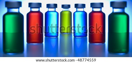 Two rows of vials filled with colored liquids. Focus on the blue ones. - stock photo