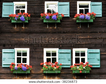 two rows of windows with flower decoration in textured wooden wall - stock photo