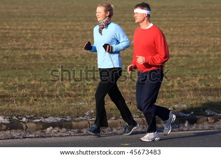 Two running in the cold winter weather - stock photo