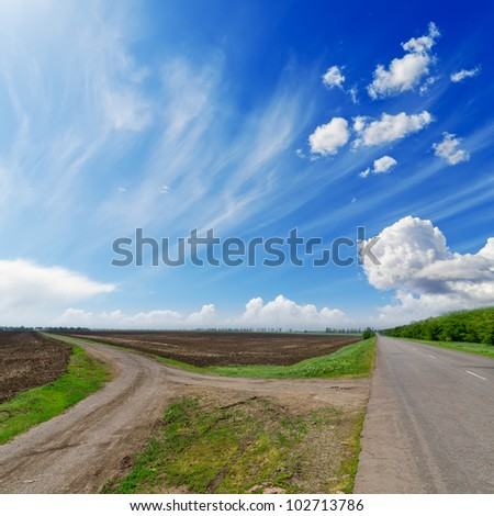 two rural road  under cloudy sky - stock photo