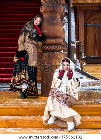 Two Russian noblewoman in Russian national dress on the porch of a wooden Kremlin