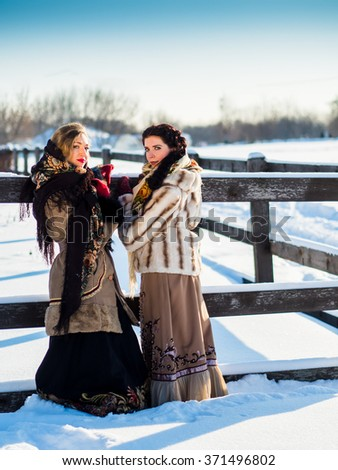 Two Russian noblewomen in Russian national clothes on a strong frost in the village near the fence