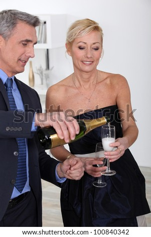 two 50's old people drinking sparkling wine - stock photo