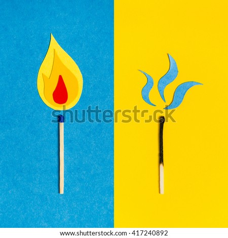 Two safety matches on colorful paper background - burning one on the blue background and the burnt out one on the yellow background - stock photo