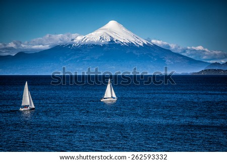Two sailboats sail in front of snow capped Orsono Volcano in Chile-Edit - stock photo