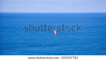 Two sailboats with red and white sails in the calm sea. (Brittany, France) Dreams come true concept. - stock photo
