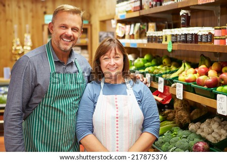 Two Sales Assistant At Vegetable Counter Of Farm Shop - stock photo