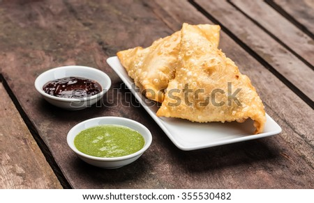 Two samosas served with mint coriander chutney and tamarind chutney - stock photo