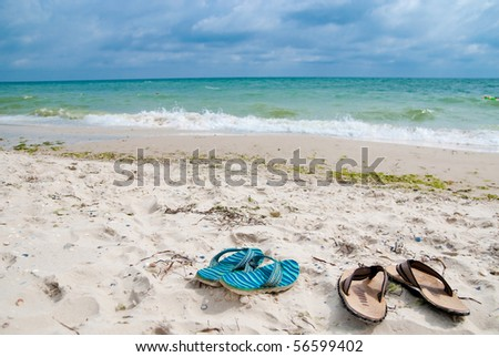 Two sandals on the beach near sea - stock photo