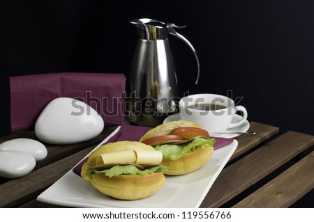 Two sandwich on white china plate, cup of tea and thermos on table - stock photo