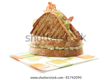 Two sandwiches: cheese and bacon and egg salad. Lie on a paper napkin. Isolated on a white background.