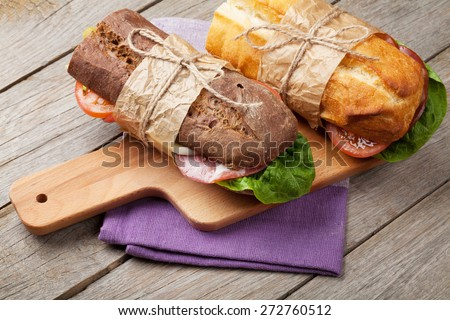 Two sandwiches with salad, ham, cheese and tomatoes on cutting board - stock photo