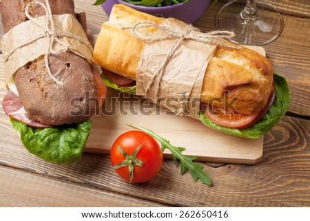 Two sandwiches with salad, ham, cheese and tomatoes on wooden table - stock photo