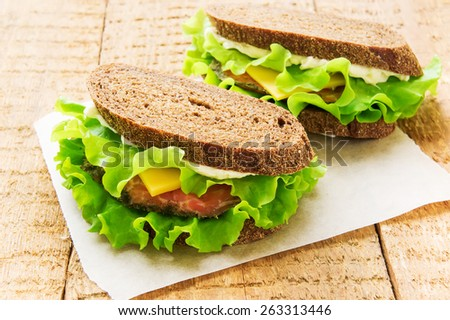 Two sandwiches with smoked salmon, cheese and salad on wooden table - stock photo