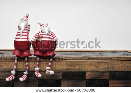 two Santa Claus are sitting on a box - stock photo