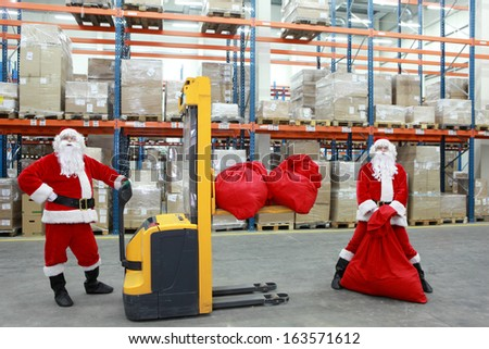 two santa clauses workers at work in large storehouse - stock photo