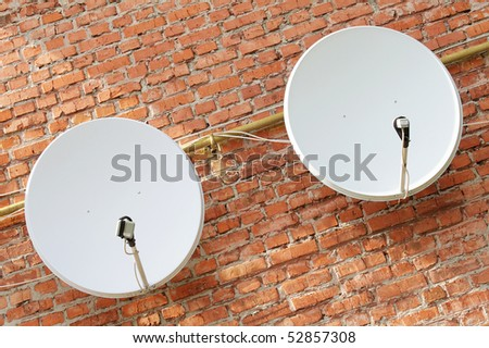 Two satellite dishes on the brick wall - stock photo