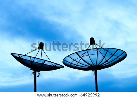Two satellite dishes sitting together on top of the high building - stock photo