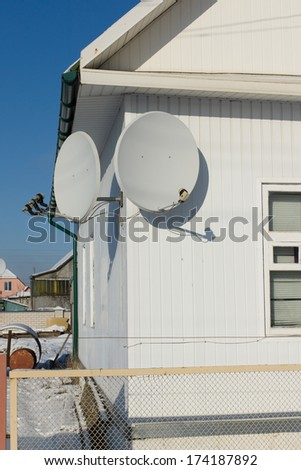 two satellite dishes to receive television transmissions installed on the wall - stock photo