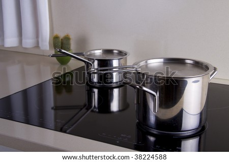 Two sauce pans in silver in a modern kitchen
