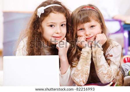 Two school aged girls lying beside laptop - stock photo