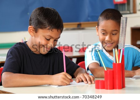 Two school boys enjoying their learning in class - stock photo