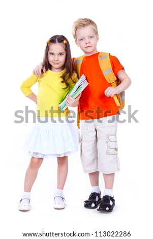 Two school children isolated on white background looking confidently at camera - stock photo
