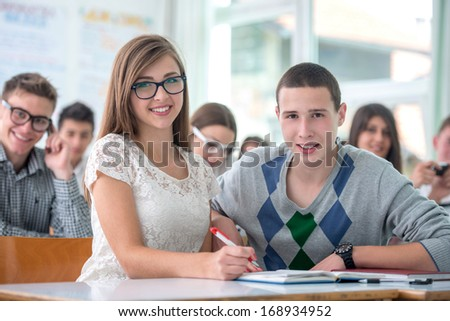 Two school colleagues posing sitting in classroom - stock photo