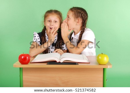 Two school girl sharing secrets  sitting at a desk from book isolated on green
