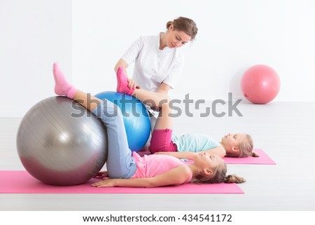 Two school girls lying on exercise mats exercising their legs on balls, accompanied by a physical therapist - stock photo