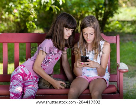 Two school girls playing with cellphone in park - stock photo