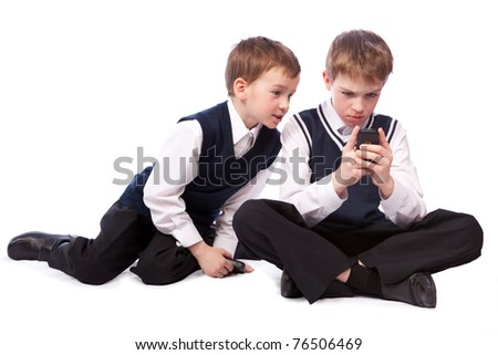 Two schoolboys play on  mobile phone, isolation - stock photo