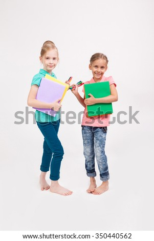 two schoolgirls on a white background with books and pens in their hands. - stock photo