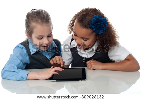 Two schoolgirls operating a digital tablet - stock photo