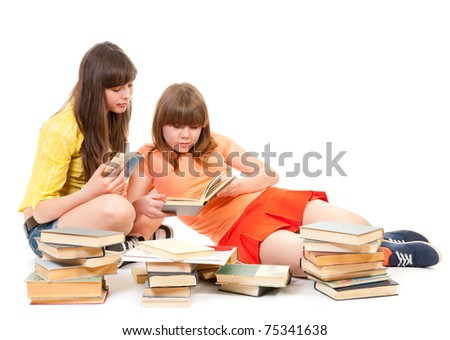 Two schoolgirls read many books isolated on white - stock photo