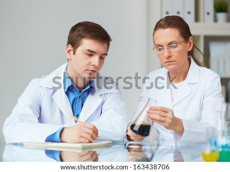 Two scientists looking at glass flask with liquid in laboratory - stock photo